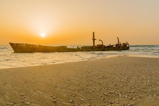 Sunset view of a rusty shipwreck in HaBonim Beach