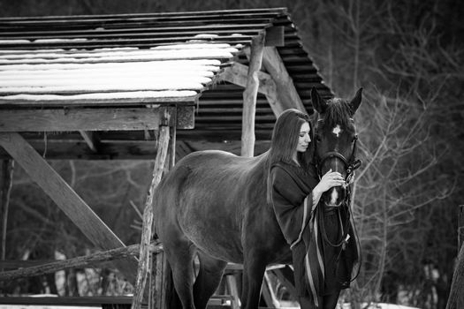 Beautiful girl hugs a horse near wooden buildings on a winter day, black and white photography