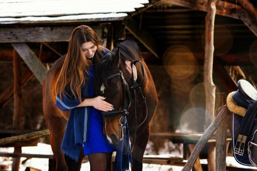 Beautiful girl in a blue stole hugs a horse near wooden buildings on a winter day