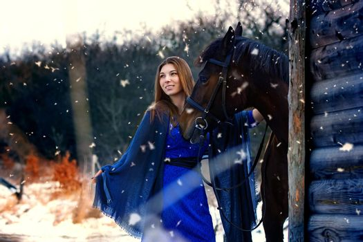 Beautiful girl in a blue stole stands next to a horse near wooden buildings on a snowy winter day
