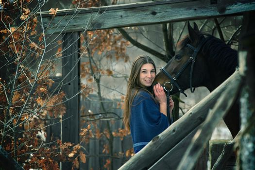 A beautiful girl in a blue stole stands next to a horse on the background of wooden buildings