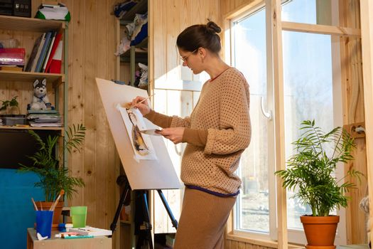 Girl artist draws on an easel at home, molubert stands at the window