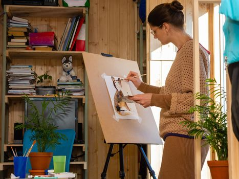 Girl artist draws on an easel at home