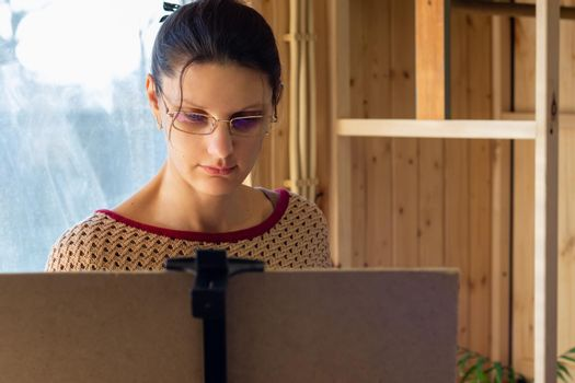 Portrait of an artist at work, a girl draws a drawing on an easel by the window, close-up