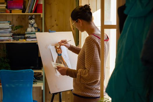 The artist paints a drawing of a cat with acrylic paints on an easel, in a small workshop by the window