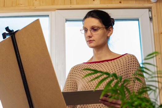 Portrait of an artist at work, a girl draws a drawing on an easel by the window