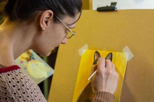 The artist draws a drawing on an easel, side view, close-up
