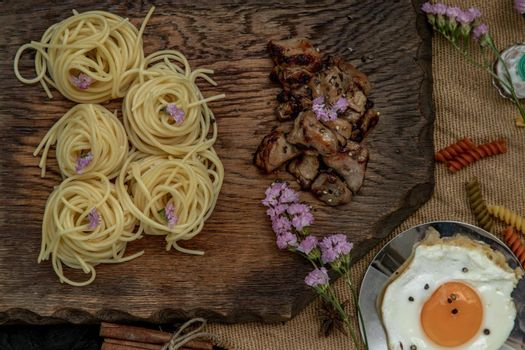Spaghetti with Roasted Chicken with Black Pepper on a wooden plate Served with Fried Egg and Crispy butter toast. Selective Focus.