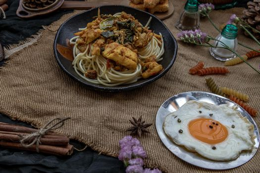Spaghetti topped with Stir fried spicy snapper on a brown plate Served with Fried Egg. Selective Focus.