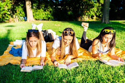 Three young women students spending time lying on meadow in city park at sunset or dawn reading book to learn university school lesson. Girl relaxing in city park enjoying preferred romance tale