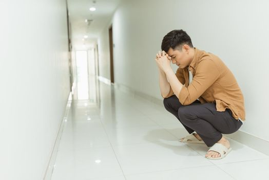 depressed man who lost faith sitting alone in a corridor