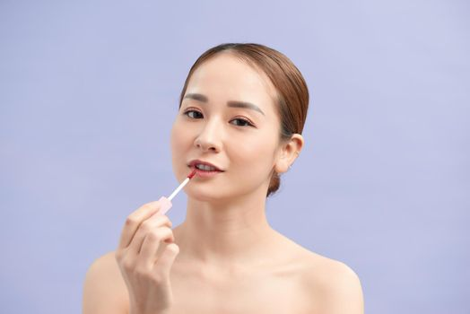 Pretty trendy stylish girl testing new lip gloss isolated on violet background, perfection, wellbeing advertisement concept