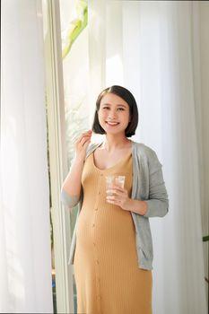 Pregnant woman taking vitamin pill