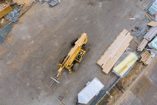 Aerial view of forklift stacker wooden material boards and beams for new house on of under construction