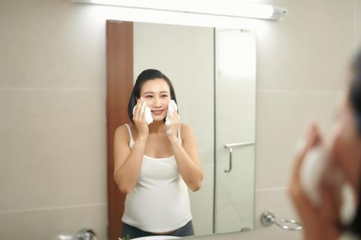 young pregnant woman washing face