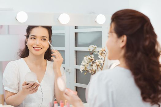 Young lady with pocket mirror using soft brush to smear eyeshadow