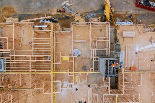 Aerial view of masonry brick builders are building walls in elevator shaft in exterior a beams house residential under construction