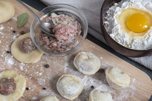 Cooking homemade dumplings, Russian dumplings with meat on a wooden table and ingredients for cooking. Rustic style. Top view
