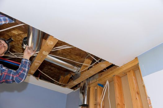 Remodelling home the installation system HVAC duct ventilation pipes in central conditioning a ceiling