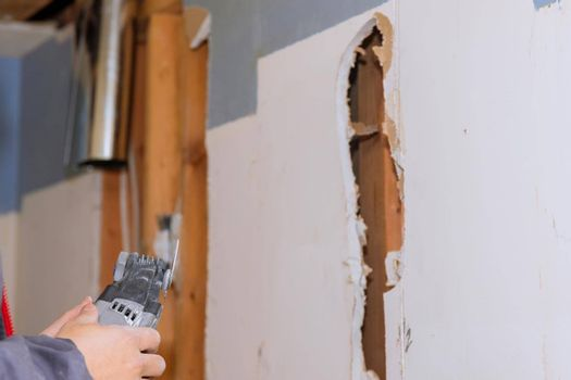 Repair of home on cutting gypsum plaster hand sawzall tool with damaged plasterboard