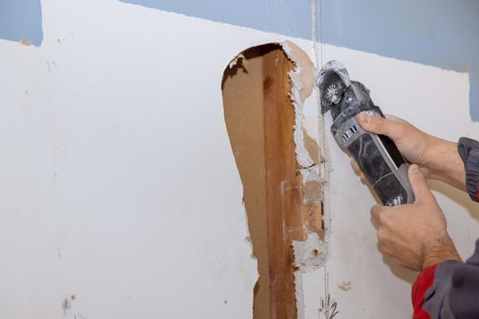 Damaged plasterboard with repair home of man cutting gypsum drywall board on using angle hand electric power tools