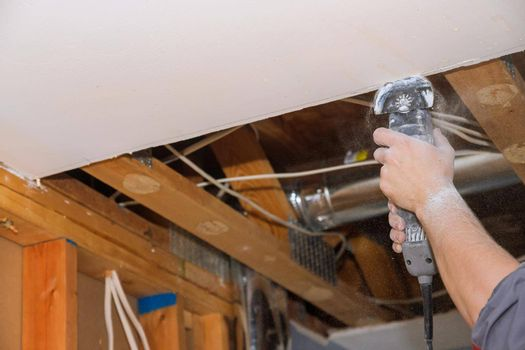 Man cutting gypsum drywall board on using angle hand electric power tools