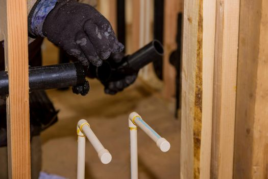 Plumbing building contractor installing plastic drain pipe in the elbow for sink drain for a custom new house