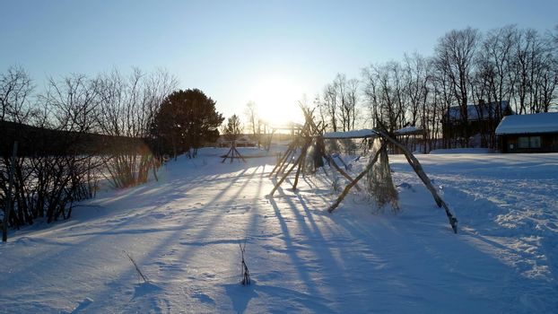 the remains of a Sami camp on the banks of the frozen lake
