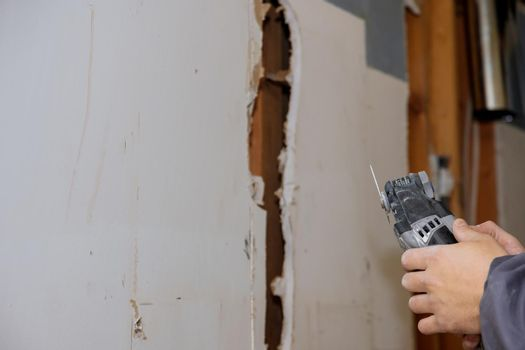 Man cutting gypsum plasterboard plaster hand sawzall tool