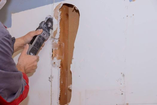 Renovation home improvement apartment interior damage for drywall board with repair home of man cutting plasterboard on using angle hand electric power tools