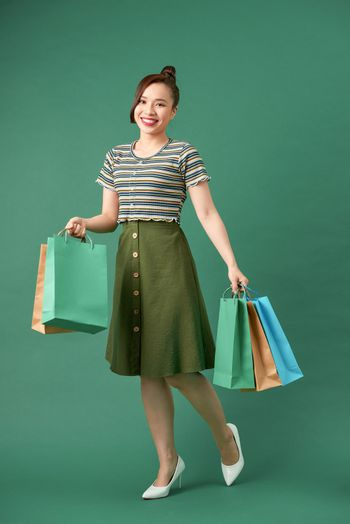 Woman shopaholic with multi-colored packages in hand