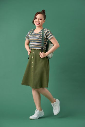 Indoor picture of young good-looking teenage girl isolated on green background,