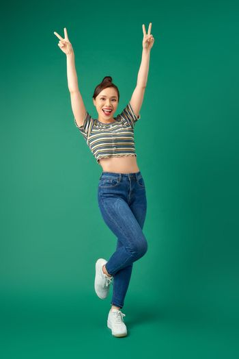Full-length portrait of a joyful attractive Asian girl celebrating success while jumping over green background.