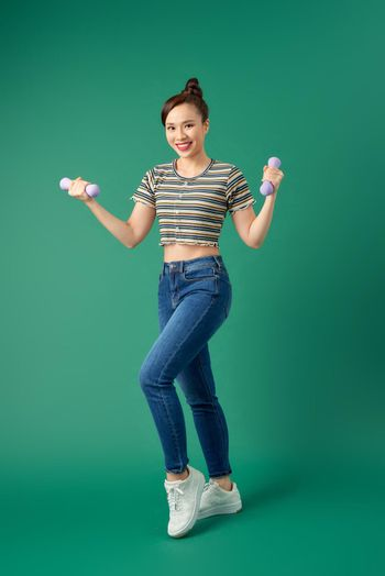 Full-length of young Asian woman holding dumbell over green background.
