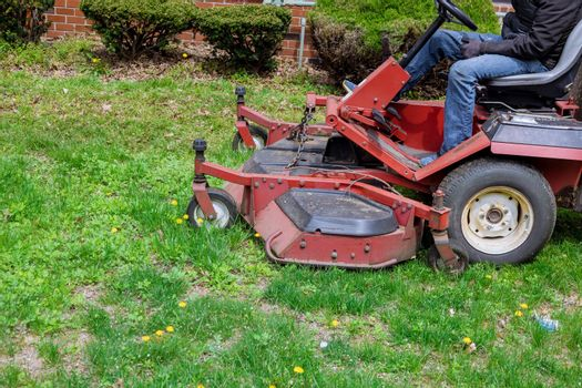 Ride-on lawnmower utility worker in lawn mower gardener cutting the grass