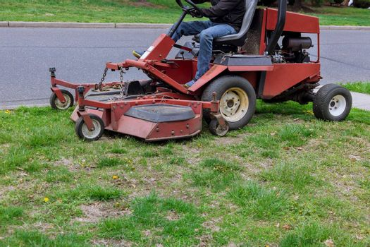 Lawn mower cutting green grass in gardening along the street