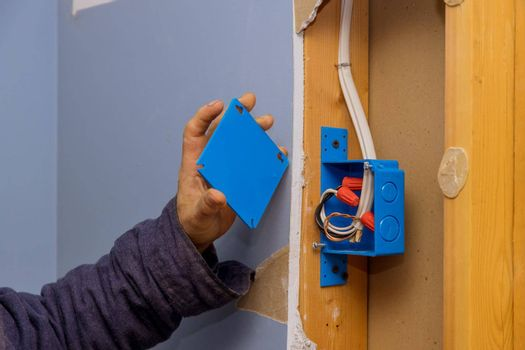 Hands of an electrician fasten the electrical box to the beams to place the electrical