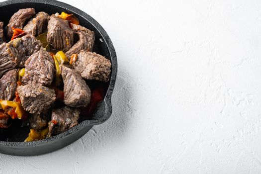 Mongolian beef, pieces of beef stewed in soy sauce, in cast iron frying pan, on white stone surface, with copy space for text