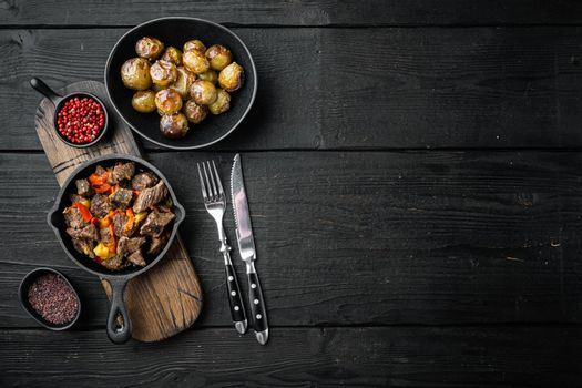 Irish stew made with beef, potatoes, carrots and herbs, in cast iron frying pan, on black wooden background, top view flat lay, with copy space for text