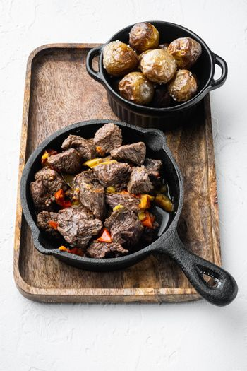 Goulash, beef stew, in cast iron frying pan, on white stone surface