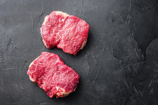 Fresh beef Rump steaks over black background, top view with space for text.