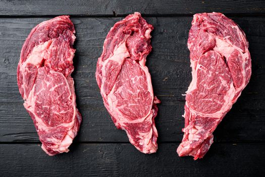 Black Angus prime beef rib eye steak, marbled meat, on black wooden table background, top view flat lay