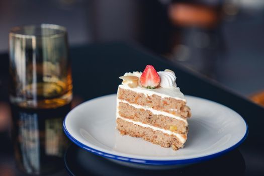 Carrot cake with strawberries topping on table.