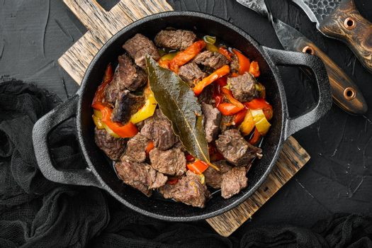 Beef stew goulash - rustic style, in cast iron frying pan, on black stone background, top view flat lay