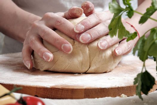 Women's hands knead the dough from wheat flour