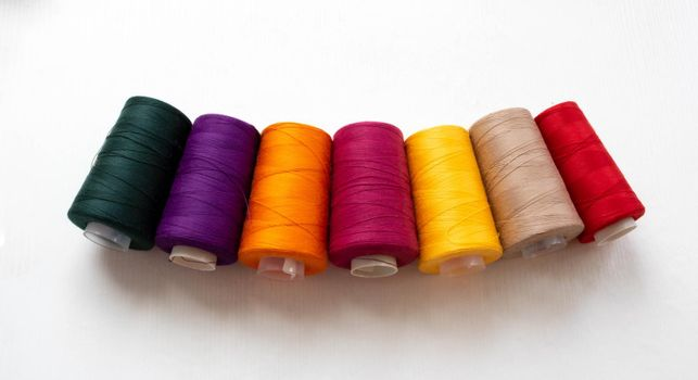 Panorama of colorful bobbins isolated on a white background.