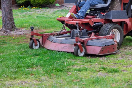 Man ride-on with lawn mower in mows green grass on adjacent territory