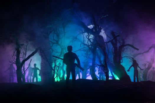 Man with riffle against zombie attack. Zombie apocalypse. Scary view of blurred zombies at the forest and spooky cloudy sky with fog. Horror Halloween concept.