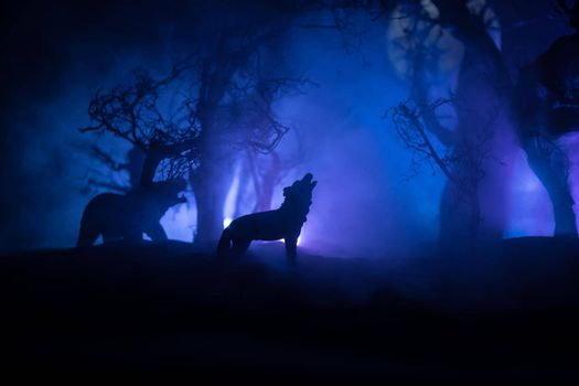 Silhouette of howling wolf and bear against dead forest skyline and full moon. Creative artwork decoration. Selective focus