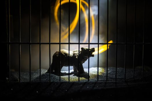 Silhouette of a Bear miniature standing in a zoo cage dreams of freedom. Creative decoration with colorful backlight with fog. Selective focus